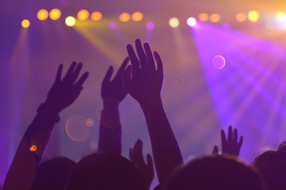 hangs waving in the air during a concert with purple and yellow lights
