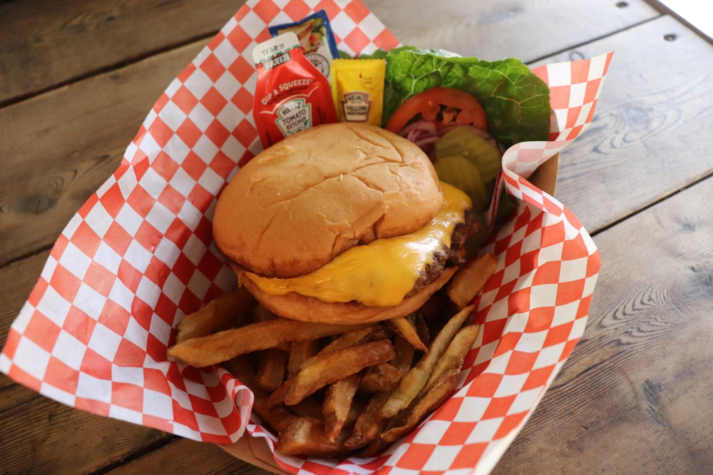 The cheeseburger and fries combo ($11) is served with lettuce, tomato, onion, pickles and condiments on the side. (Photos By Zara Flores/Community Impact Newspaper)