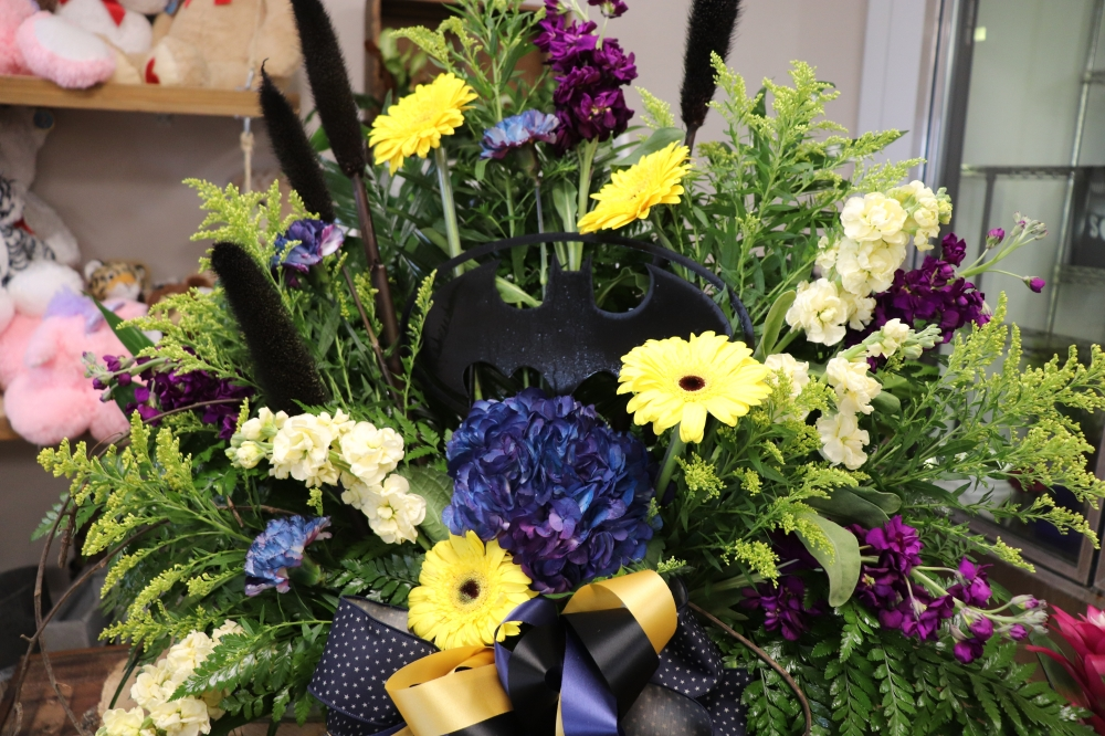 Shoppers can customize bouquets with additions like this Batman emblem. (Photos by Zara Flores/Community Impact Newspaper)