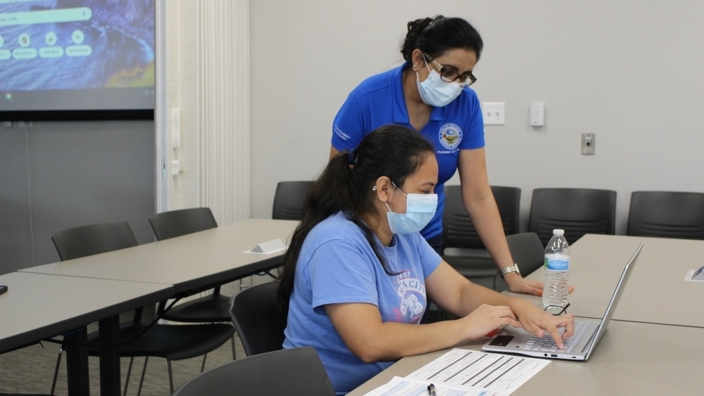 Dr. Amardeep Gill, professor of Population Focused Community Health, assists nursing student Thania Colocho with an assignment in the Health Sciences Center at Collin College's McKinney campus. (Brooklynn Cooper/Community Impact Newspaper)