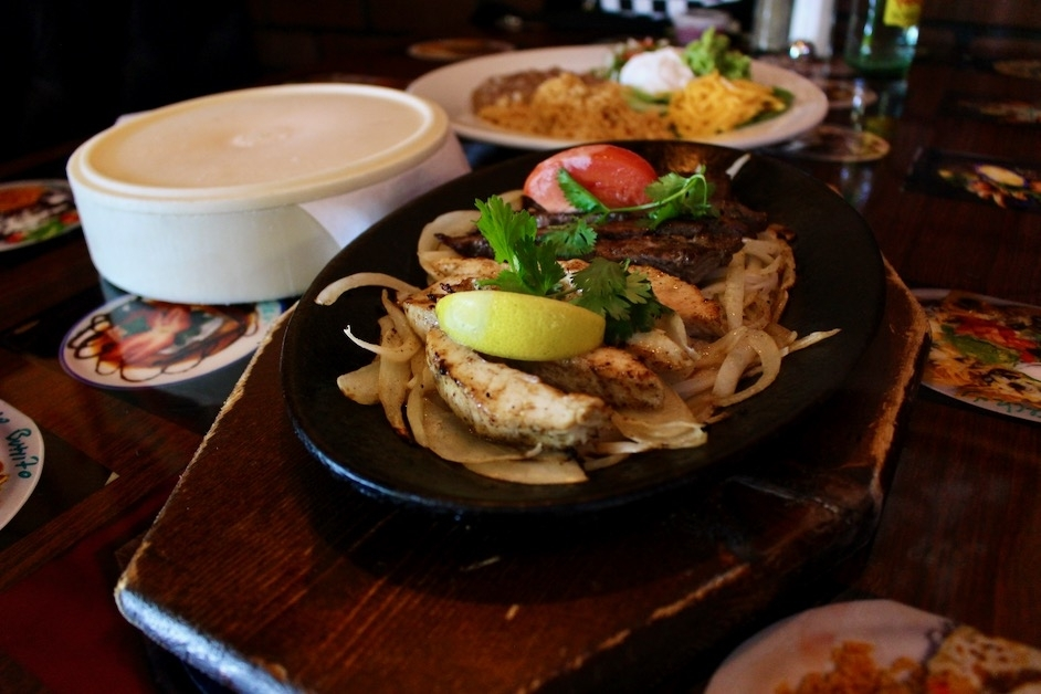 The mixed fajitas ($10.99) come with grilled chicken and steak with sauteed onions. The dish is served with guacamole, rice and beans. (Chandler France/Community Impact Newspaper)