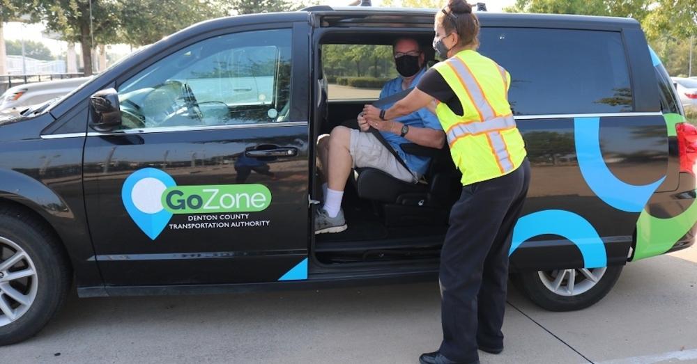 driver helping rider into van