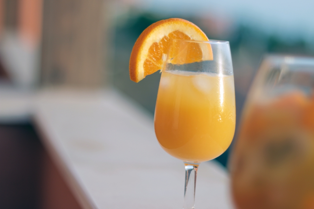 mimosa with orange slice in wine glass at brunch