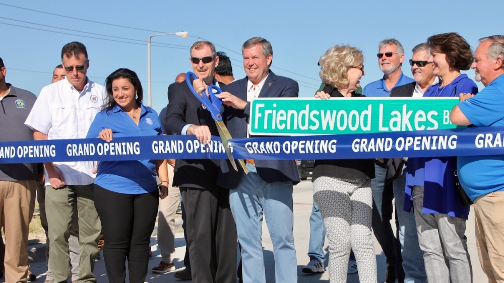 Friendswood mayor Mike Foreman holds the scissors for the ceremonial ribbon cutting of the new Friendswood Lakes Boulevard extension. (Andy Yanez/ Community Impact Newspaper)