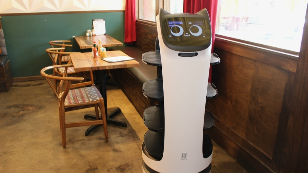 The robot server at Layered in McKinney is programmed to carry food on its tiered built-in trays to diners. (Miranda Jaimes/Community Impact Newspaper)