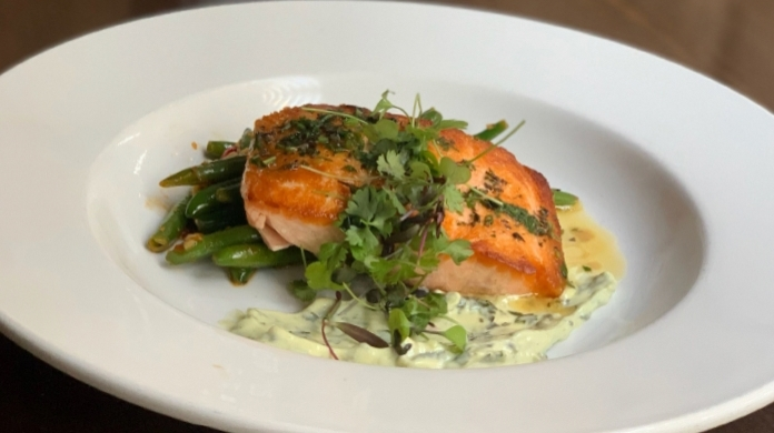The pan-seared salmon ($22) is braised with white wine and comes with lemon butter, roasted red peppers, green beans and a basil aioli. (Erick Pirayesh/Community Impact Newspaper)