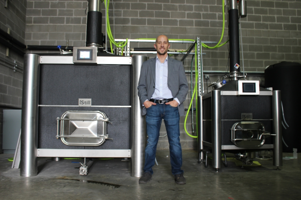 Fox & Seeker Distilled Goods co-founder and owner Sean Anger stands in front of a pair of distillers used to help create the business's spirits, which include Texas vodka, London dry gin, Texas whiskey and Meridian gin. (Wesley Gardner/Community Impact Newspaper)
