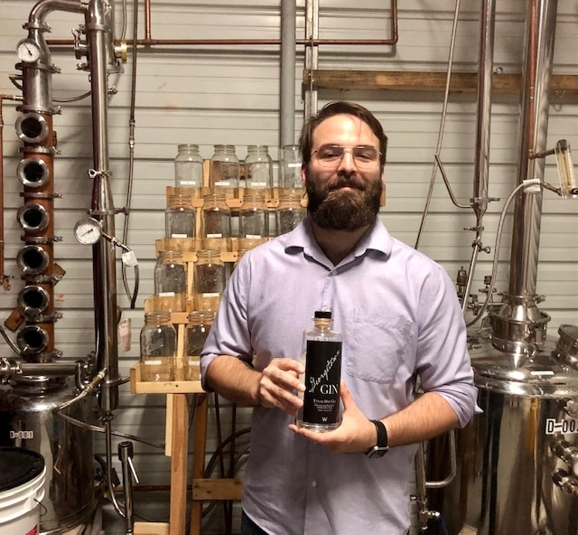 A.W. Craft Distillery owner Andrew McClellan holds a bottle of his Georgetown Texas Dry Gin. (Brittany Andes/Community Impact Newspaper).