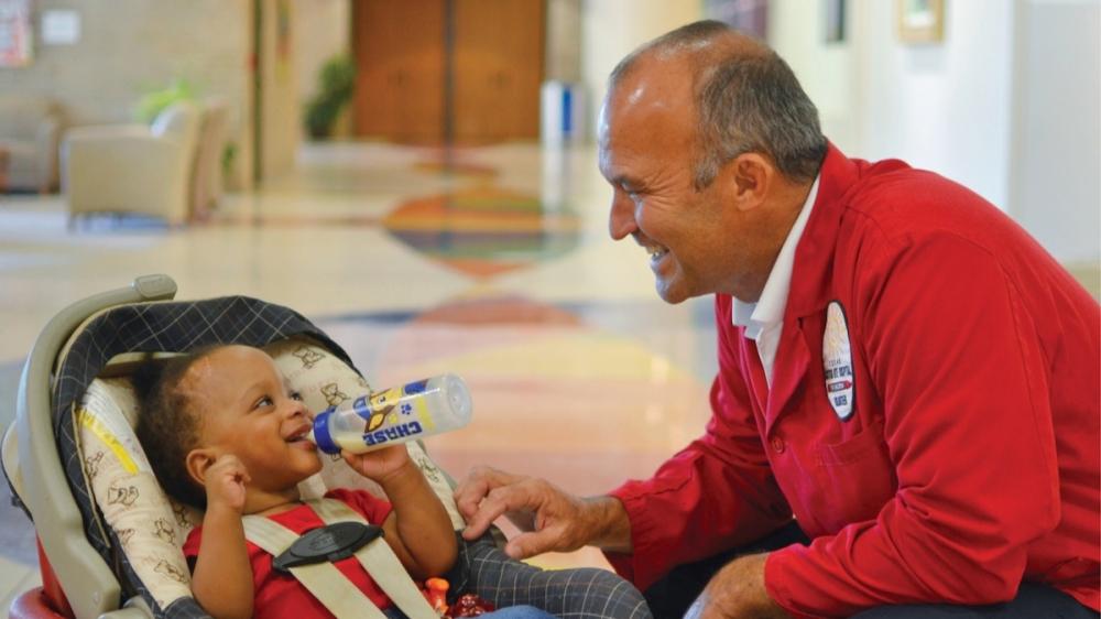 man feeding a smiling baby