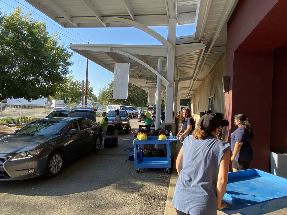 Volunteers load food into vehicles for deliveries.