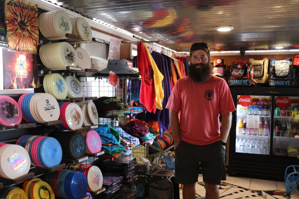 Owner Michael Lambert stands in the Pro Shop, a converted 1957 Spartan Travel Trailer. (Photos by Zara Flores/Community Impact Newspaper)