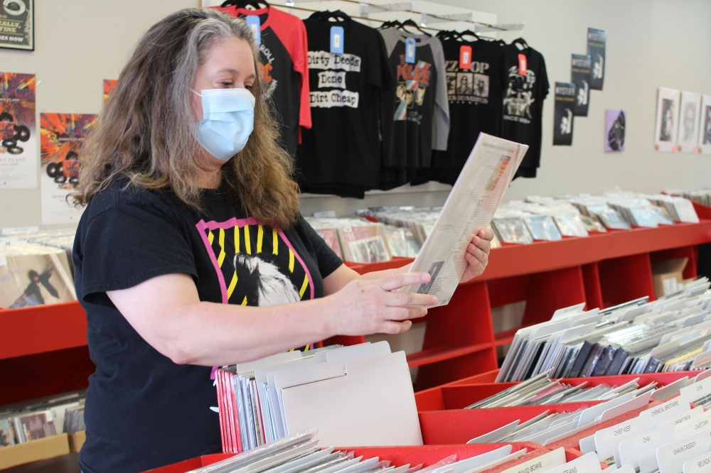 Volume Music owner Tiffany Cochran goes through vinyl records at her store. (Andrew Christman/Community Impact Newspaper)