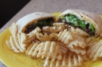 The quesadilla burger ($12) comes wrapped in a homemade flour tortilla. (Colleen Ferguson/Community Impact Newspaper)