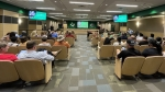 A group of people attend a Carroll ISD school board meeting