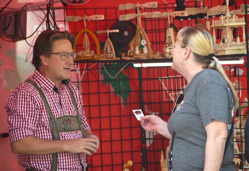 Kurt Schmidt talks to festival-goers about Schmidt Christmas Market at Oktoberfest on Oct. 17.
