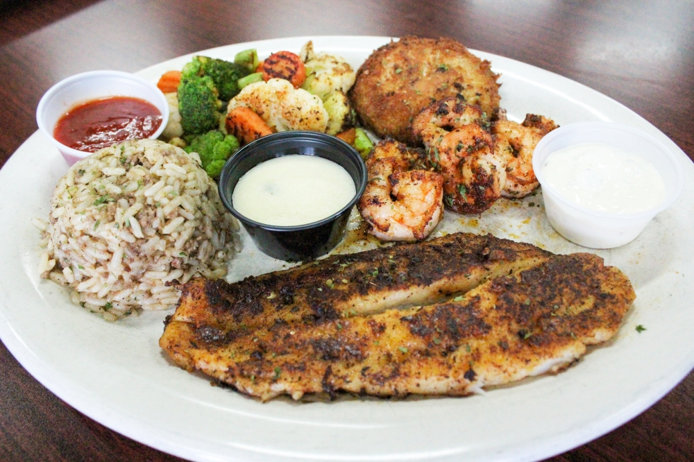 The Seafood Platter ($20.99) comprises a crab cake, a catfish filet and six blackened shrimp served with dirty rice and a side of veggies. (Hannah Zedaker/Community Impact Newspaper)
