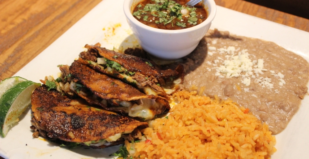 Birria Tacos are served on Tuesdays at Los Compadres. Traditional slow-cooked tender beef in dipped corn tortillas is topped with cilantro and onions. The tacos are served with Mexican beef stew, rice and beans. (Sandra Sadek/Community Impact Newspaper)