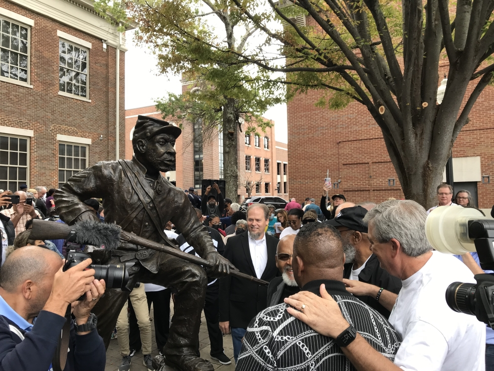 Members of the Fuller Story initiative gather around the newly unveiled statue. (Wendy Sturges/Community Impact Newspaper)